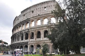Photo: Koloseum. Na konci ulice Fori Imperiali, mezi vrchy Esquilin, Palatin a Celio, stojí jeden z největších divů římské civilizace, KOLOSEUM. S výstavbou tohoto obrovského amfiteátru, jehož impozantní zbytky i dnes budí obdiv k antické majestátní kráse, začal císař Vespasianus v roce 72 n.l. a dokončil ji jeho syn Titus v roce 80. Jako otroci pracovali na stavbě Kolosea židovští zajatci. Stavba by se měla správně nazývat Fláviovský amfiteátr, ale Římané začali říkat amfiteátru Koloseum jednak kvůli samotným rozměrům nové stavby, jednak kvůli soše Neronova Kolosu, která stála kdysi v sousedství amfiteátru.