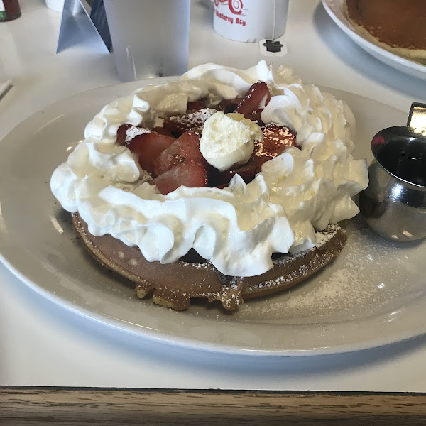 Gluten free waffle with strawberries and whipped cream