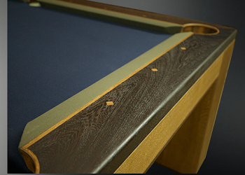 the end of a pool table with dark and light wood with dark blue felt