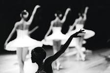 3 balerina's met wervelend wit jurkje achter een deels zichtbare, onbelichtte, balerina