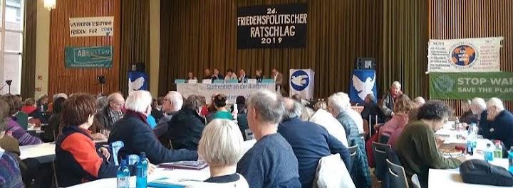 Menschen im Saal. Transparent: «26. Friedenspolitischer Ratschlag 2019».