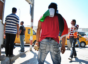 Photo: A young Palestinian prepares to launch a stone during a demonstration at Qalandiya checkpoint.