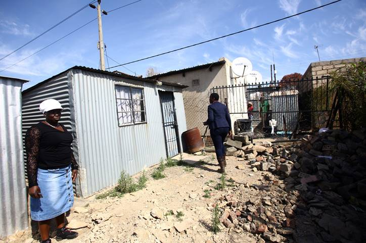 Ivory Park residents Elizabeth Matseba and her daughter Tabang Matseba stand next to a shack that used to be in their yard before the fencing was moved back by illegal land invaders demanding the space where the shack is situated.