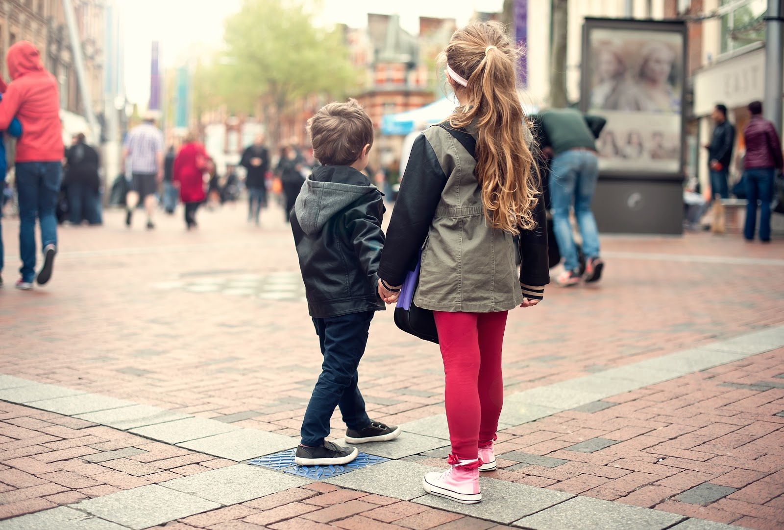 A young boy and girl walking alone in a crowded public square