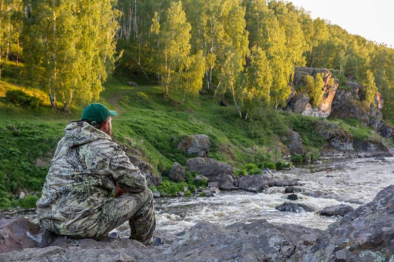 Раздумывающий человек на фоне реки с порогами