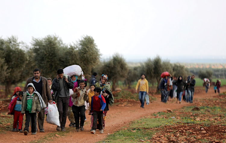 Internally displaced people walk with their belongings in the town of Inab, eastern Afrin, Syria.
