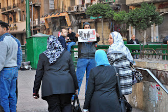 Photo: A man holds up the latest issue of the independent newspaper 'Tahrir', which displayed on its cover the now infamous photo of army soldiers ruthlessly beating and stripping a veiled woman in the streets.