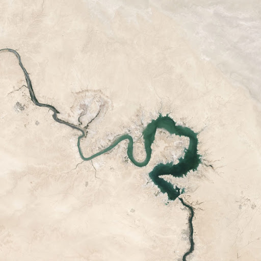 Aerial view of a snaking green river through a tan desert