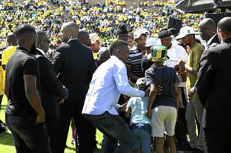 Bodyguards in black suits surround Duduzane Zuma as he embraces two boys during the ANC 108th anniversary event in Kimberley last month. He represented his father at the celebration.