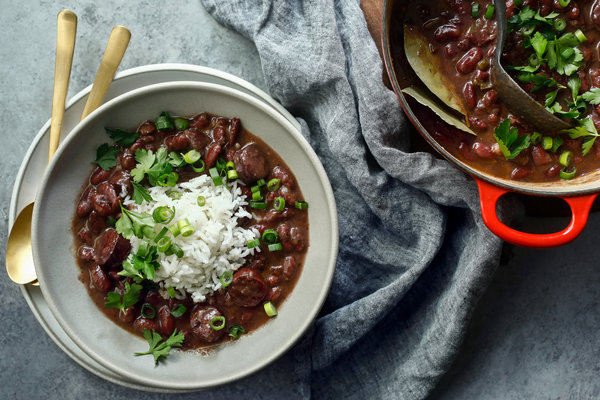 Red beans and rice that's garnished with green onions and parsley served in a bowl