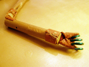 Photo: Leather is held in routered notches, and wrapped around the dowel, bonded by wood glue.