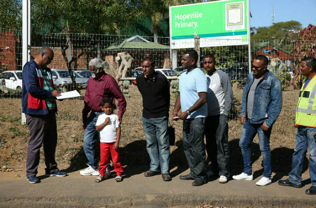 Parent Tony Govender adds Sigamoney Kisten and his grandson, Dre'n Chengelrayen, to the list he has made of people queuing outside Hopeville Primary to ensure places for next year. Parents and grandparents are camping out to register their children