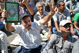 Photo: A very intense looking man holds a Quran in one hand and a 'peace' or 'V for victory sign' on the other.