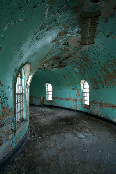 Photo: In designing Buffalo State Hospital - or, at the time, the New York State Asylum for the Insane at Buffalo - H. H. Richardson relied heavily on the writings of Thomas Story Kirkbride and the advice of Utica State Hospital administrator John P. Gray. Both stressed the need for adequate fireproofing within the building, as well as for limited access between wards. To these ends, Richardson designed the connector hallways in between the different ward pavilions with a curve dramatic enough that the halls would be useless for storage. This proved to be a visionary design move; by the 1910s, the hospital was so overcrowded that even the attic was packed with patients - and yet, no beds could be placed in these hallways, which had a heavy fireproof door at either end. The two doors would also limit access to those members of the staff with a reason to move between pavilions - patients and orderlies could not move about the complex freely.