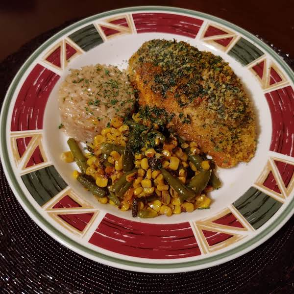 Panko Encrusted Stuffed Chicken Breast With Herb Butter Served With Risotto And Pan-seared Corn And Green Beans.