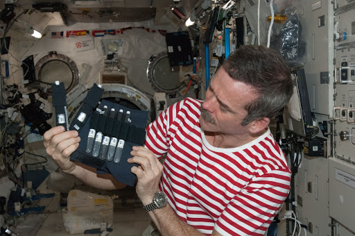 Hadfield holds bubble detectors for the RaDI-N Experiment in the Columbus Module