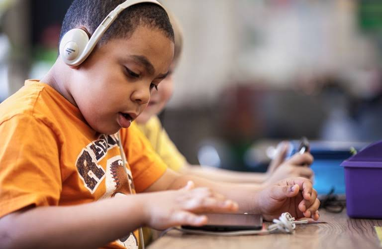 A student wearing headphones is deeply immersed in a lesson on his Chromebook tablet.