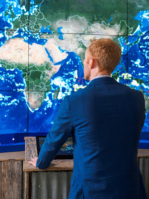 A man in a blue suit stands in front of a large digital map of the Earth.