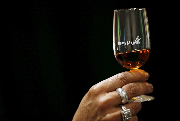 A woman holds a glass of Cognac at the Remy Martin headquarters in Cognac, southwestern France. Picture: REUTERS