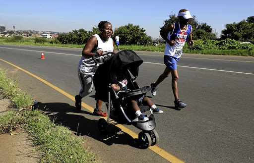 Modiehi Lephuthing runs 21km while pushing her son Lehlohonolo during the Township Marathon in Eldorado Park. / SANDILE NDLOVU