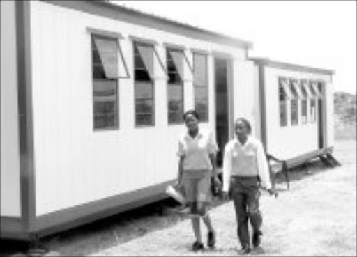 TEMPORARY SOLUTION: Two pupils at Dr AMS Makunyane High School in Seshego, near Polokwane, walk to thier mobile classroom. Pic. Edward Maahlamela. 15/01/2007. © Sowetan.