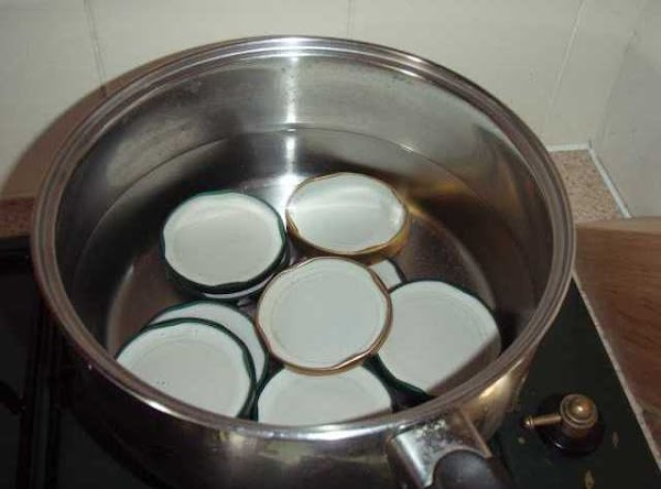 Rinse lids in hot water and place top down in a saucepan.  Cover...