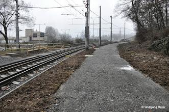 Photo: Geschotterter Weg neben den U-14-Gleisen. Links das Wasserkraftwerk, hinten die Berger Kirche