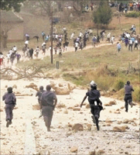RUNNING WILD: Armed police officers chase after protesters who had been throwing stones at them yesterday. The community is demanding tarred roads at OG village near Nelspruit. Pic: RIOT HLATSHWAYO. 16/09/2009.  © Sowetan.