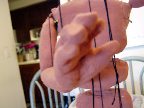 Photo: String through the hand. Everywhere else so far, I tied the string to a bit of toothpick which fits in a trench dug in the puppet. But in the hand, I made two holes and tied the string together at the top.