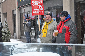 Photo: A few workers take a break from the march to enjoy a pint of beer.
