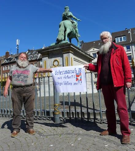 Zwei Ostermarschierer, ein Plakat trennt sie mit 2m Abstand: «Ostermarsch 2020 nur virtuell? Kriege bleiben reell!».