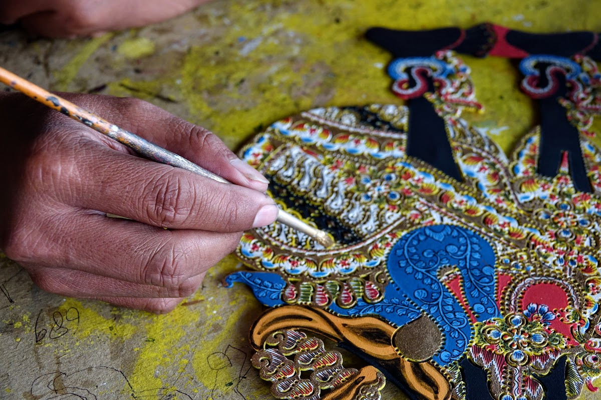 Indonesia. Crafts . Close-up on painting the leather puppet