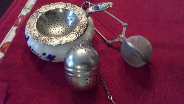 A tea strainer and two tea infusers