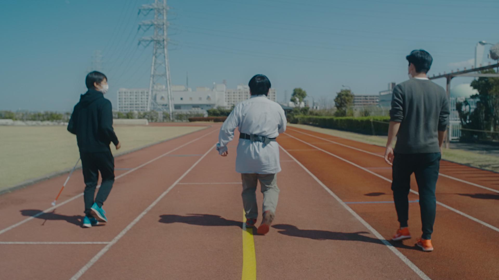 写真:コース上に貼られた黄色いガイドラインのテープに沿って歩く男性のテスト走者と、その周りを見守るスタッフ。