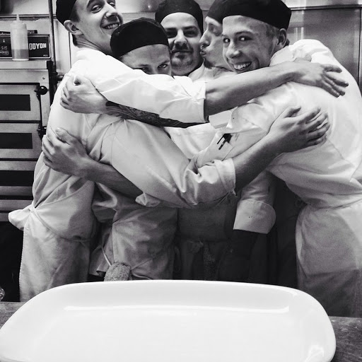 Black and white image of kitchen partners in a group hug