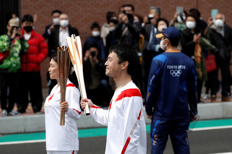 Torchbearer Junko Ito hands the torch to the next torchbearer Yoshikazu Nishikata during the Tokyo 2020 Olympic torch relay on the second day of the relay in Fukushima, Japan March 26, 2021. A fourth wave of Coronavirus is threatening the games.