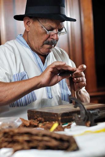 Cuba-Man-Rolling-Cigars.jpg - Cigar rolling is an art in Havana, Cuba.