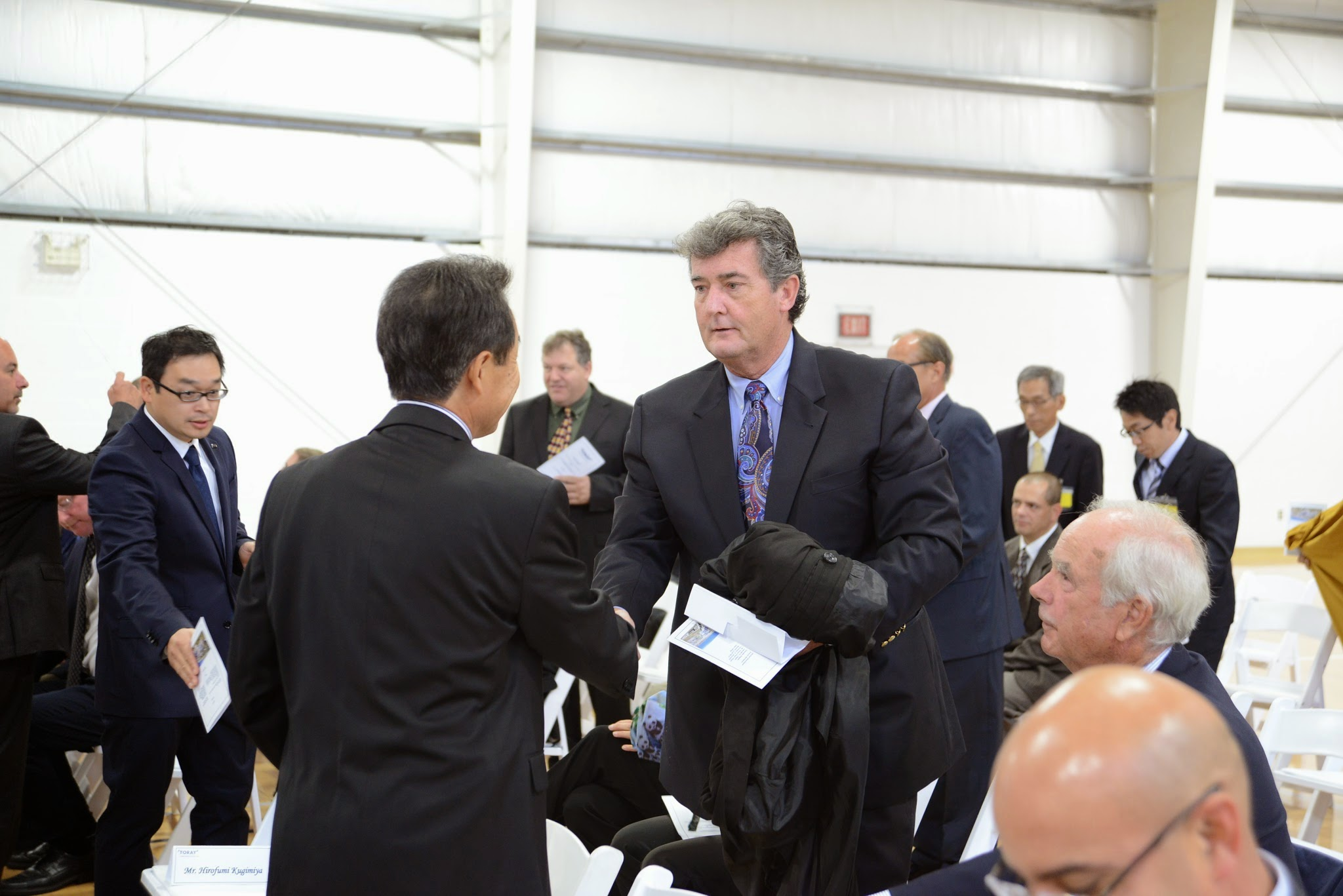 Photo: Rep. Robert Craven greets officials from Toray Plastics at the commissioning of the company's co-generation facility in North Kingstown on September 25, 2014.