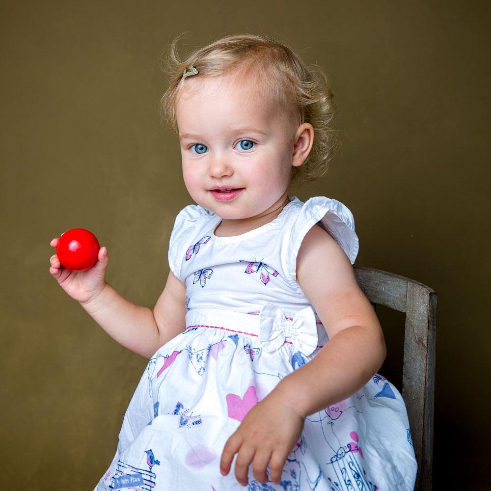 Ein Mädchen mit einer roten Kugel.