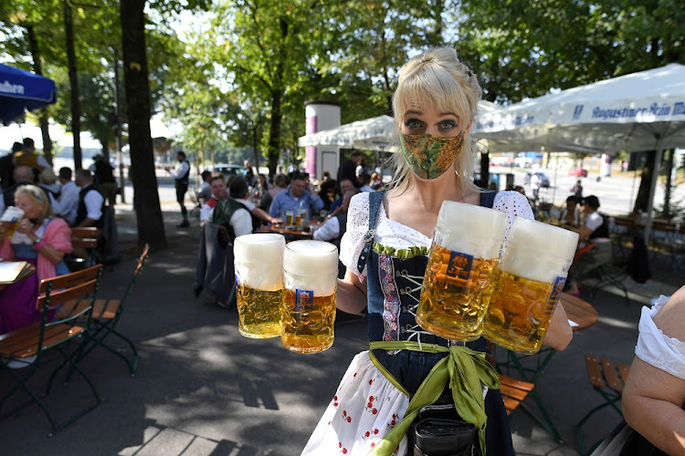 A server carries mugs at a beer garden near Theresienwiese where Oktoberfest would have started on Saturday as Covid-19 continues in Munich.