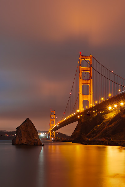 Photo: The iconic Golden GAte Bridge, shot from Frot Baker.  There was a full moon this evening, but it was accompanied by the fog as well.  While the moon was obscured most of the time, it did light the clouds nicely in the background.
