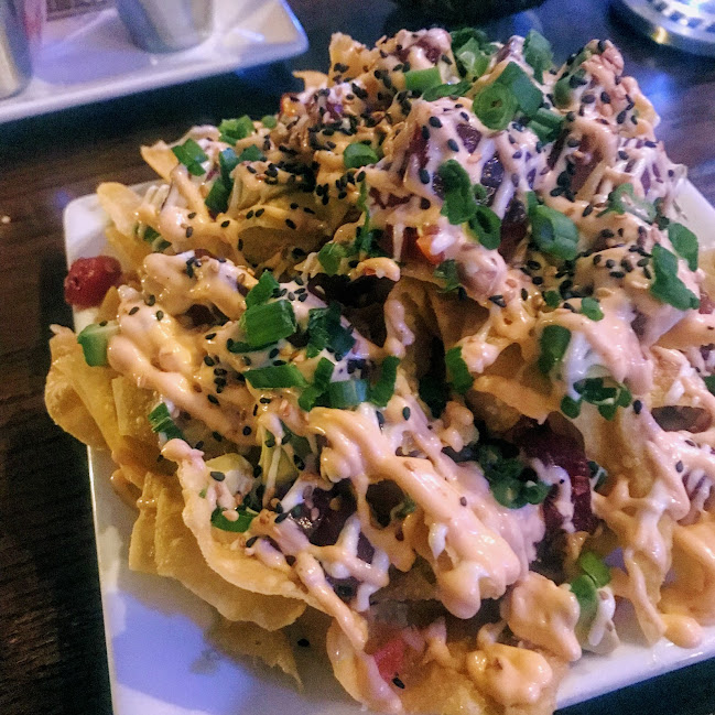 Ahi poke nachos with chopped avocado, red bell pepper salsa, wasabi, and sriracha aioli over wonton chips, Sam's Ocean View