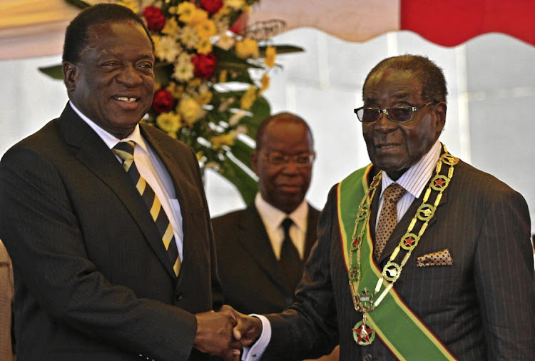 Emmerson Mnangagwa, left, now president of Zimbabwe, shakes hands with Robert Mugabe.