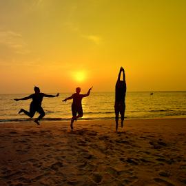Enjoyment on beach by Manoj Kulkarni - Landscapes Beaches ( water, sand, jumping, enjoying, silhouette, malvan, sea, ocean, quiet, beach, yellow, landscape, jump, sky, vacation, sunset, india, maharashtra, light, evening, black, golden,  )