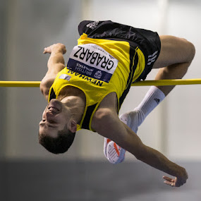 Grabarz goes for Gold.  by Ron Russell - Sports & Fitness Running ( concentration, winning, jumps, athletics, fosbury flop, leader, male, arching, indoors, winner, clearance, high jump, sports action )