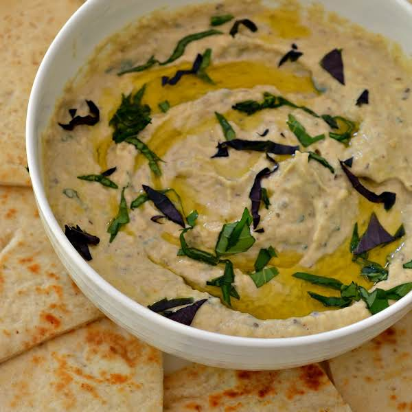 Baba Ganoush Is A Simple Middle Eastern Dip Made With Roasted Eggplant, Tahini, Lemon Juice, Garlic And Other Delectable Seasonings.  It Is Traditionally Served With Warm Pita Bread.