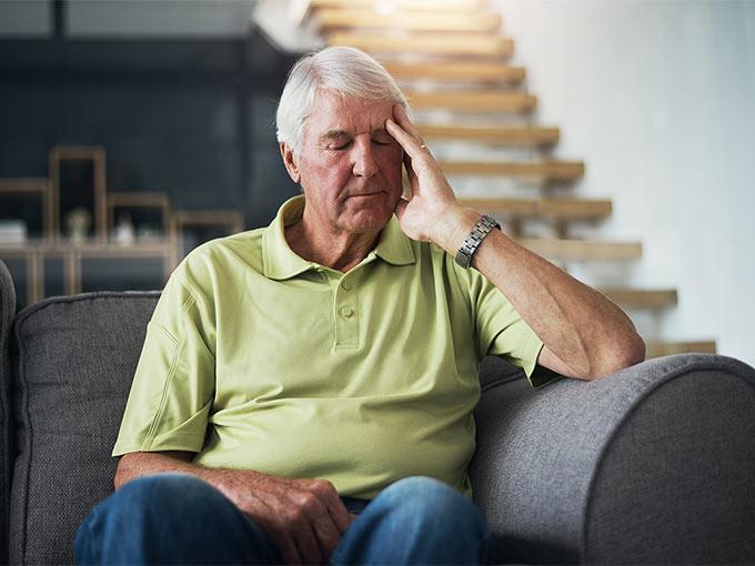 Ein älterer Mann sitzt mit geschlossenen Augen auf einem Sofa und stützt sich den Kopf - er leidet durch Diabetes an Müdigkeit.