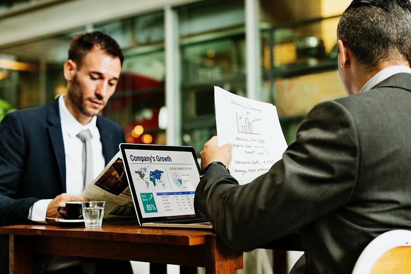 Duas pessoas sentadas em uma mesa lendo relatórios.