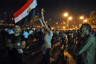 Photo: An Egyptian flag waves in the air as protesters express outrage at the military's killing over 25 civilians...