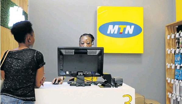 An employee attends to a customer at an MTN shop in Johannesburg.